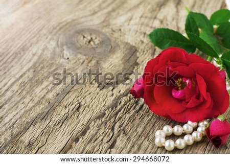 Fresh red roses on old wooden background. Selective focus. Place for text. Toned image. - stock photo