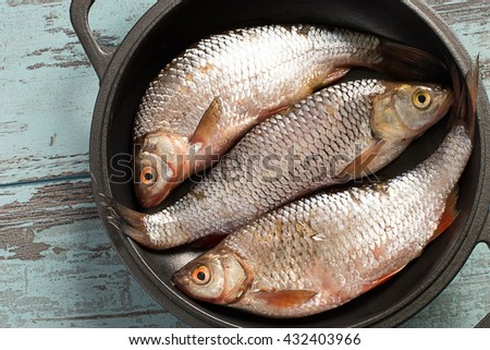 Fresh river fish in a frying pan on a blue wooden background.