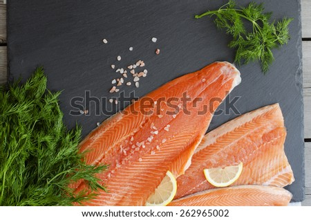 Fresh salmon fillet with aromatic herbs, spices, pink salt  and lemon. Healthy food, diet or cooking concept. - stock photo