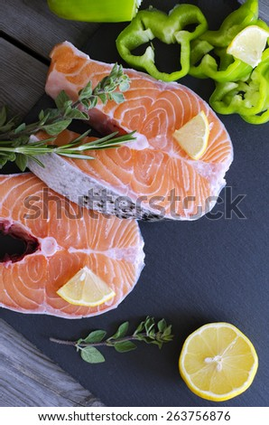 Fresh salmon steaks with aromatic herbs, spices, peppers  and lemon. Healthy food, diet or cooking concept. - stock photo