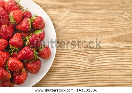 Fresh strawberry in the plate on wooden background