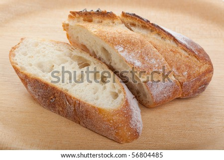 Freshly cut baguette on a wooden plate - stock photo