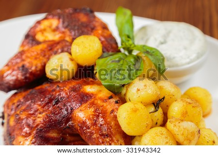 Fried potatoes with chicken legs. Hearty and delicious. Beautiful exhibition dish in white plate. Photo for culinary magazines, posters and websites. - stock photo
