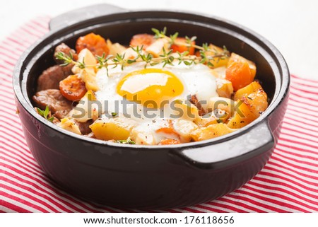 Fried potatoes with meat, bacon, mushrooms and a fried egg - stock photo