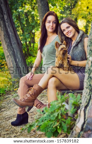Friends in the park / Beautiful girlfriends are in the park with their dog, in autumn