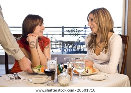 2 friends sitting at a table having lunch being served salad - stock photo