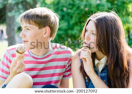 2 friends young woman & handsome boy eating ice cream having fun happy smile on summer green outdoors copy space background portrait picture - stock photo
