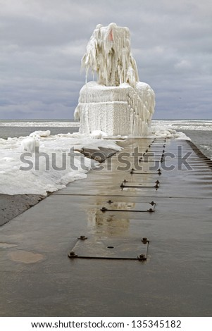 """Frozen Light"" -- Ice consumes the South Light at St. Joseph along Lake Michigan. - stock photo"
