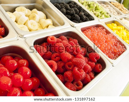 �¢??Frozen yogurt toppings bar. Yogurt toppings ranging from fresh fruits, nuts, fresh-cut candies, syrups and sprinkles. - stock photo