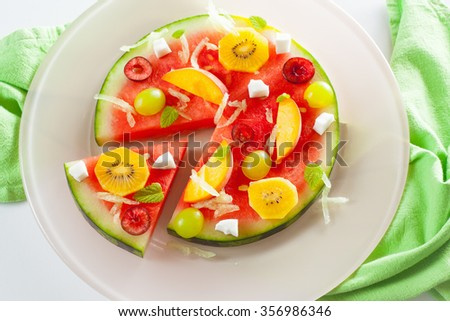 Fruit pizza on a watermelon base with yellow kiwi, peach, grape, cherry and rasped melon and grated coconut  on a pink plate on a green background, horizontal - stock photo