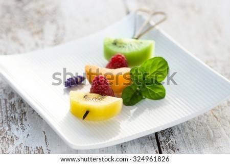 Fruit skewer on a white platter  - stock photo