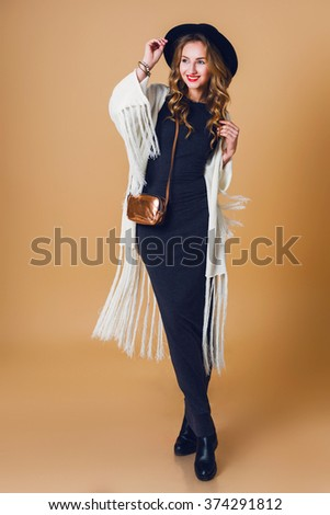 Full length image of young blonde  girl  in black wool hat  wearing oversize  white fringe  poncho with long grey dress. Studio shot. American hippie bohemian style.   - stock photo