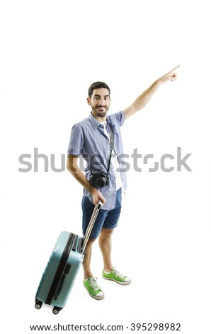 Full length of young male tourist standing with suitcase, pointing to the side, Isolated on white background  - stock photo
