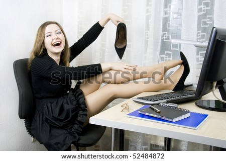 Fun woman a black dress and taking off shoes - stock photo