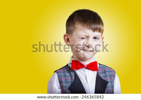 Funny little boy with one eye closed isolated over yellow background.