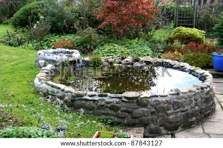 Garden Pond with small trickle waterfall - stock photo