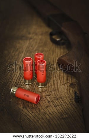 12 gauge ammunition on the floor with shotgun. This is the steel version of the ammunition.Used for hunting birds and small wild animals. - stock photo