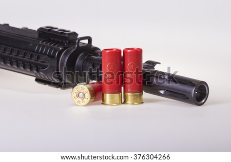 12 gauge shotgun shells used for hunting with assault riffle on gray gradient background - stock photo