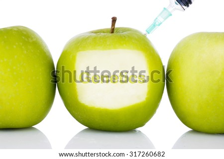 """Genetics"" text on green apple with syringe injected on it isolated white background - concept for genetically modified foods for diet,future health, science, chemistry, medicine and people. - stock photo"