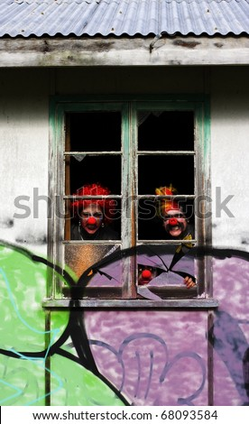 3 Ghoulish Clowns Stare Peering Out Of The Darkness Inside The Haunted House Of Horrors - stock photo