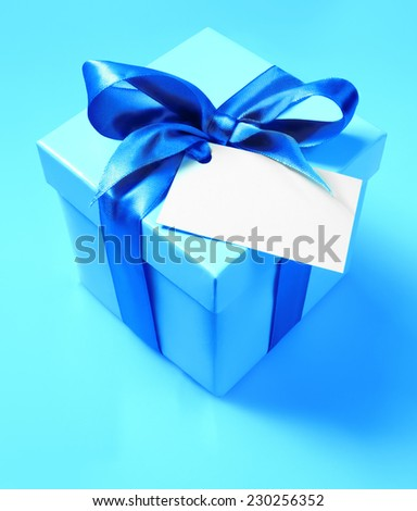Gift blue box with ribbon and empty label for your text