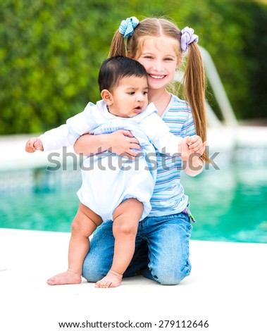 girl and a boy on the background of the  pool - stock photo