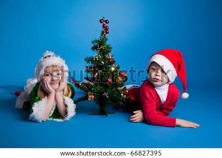 girl and  boy lying near a New Year tree - stock photo