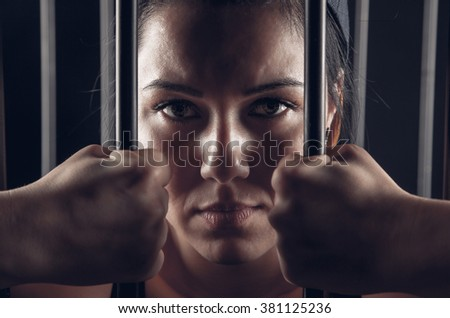 girl behind bars in jail - stock photo