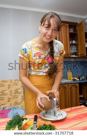 Girl grating coconut  in the kitchen