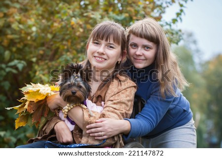 girl in wheelchair with her little dog and girlfriend smiling into the camera in the park on autumn  day - stock photo