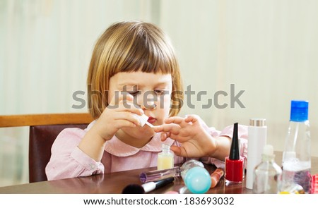 girl paints her nails on the hands - stock photo