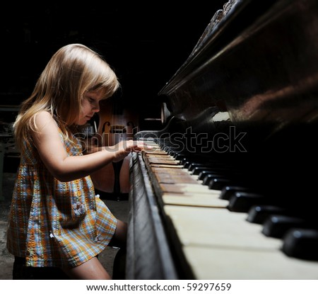 girl playing on an old black piano