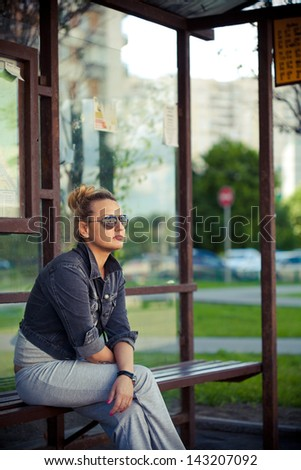 Girl sitting at the bus stop - stock photo