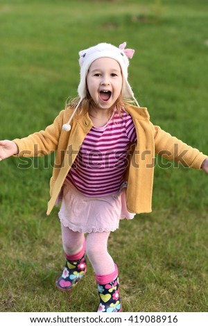 girl spinning on the grass - stock photo