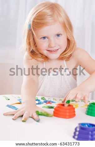 girl with colorful paints ready for hand prints