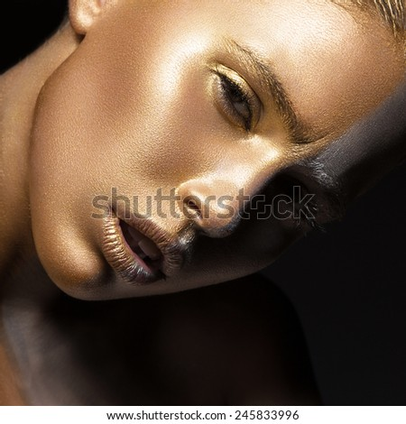 Girl with gold and silver skin in the image of an Oscar. Art image beauty face. Picture taken in the studio on a black background. - stock photo