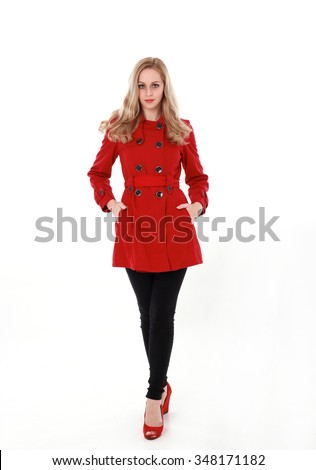 glamorous, beautiful blonde young woman with blonde hair, wearing  long, red winter trench coat.  full length standing portrait, hands in pockets, legs crossed. isolated on white background. - stock photo