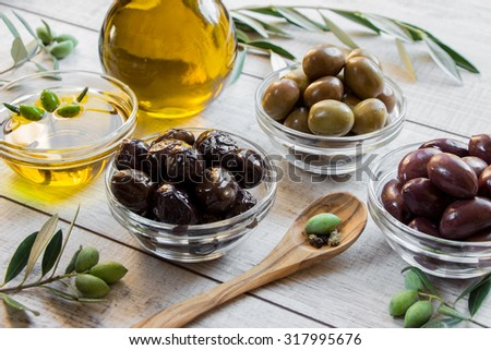 3 glass bowls with different kinds of olive, bowl with olive oil, bottle of olive oil, wooden spoon with olive, framed by branches of the olive tree on wooden white background. Olives and olive oil.   - stock photo