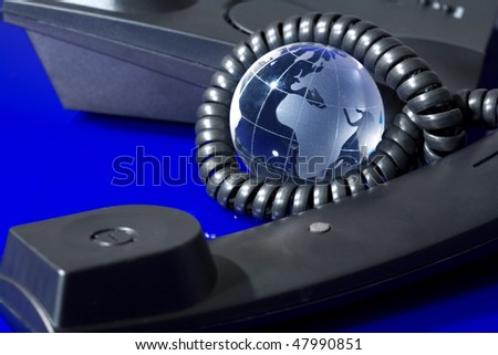 Glass globe with phone. Global communication concept. - stock photo