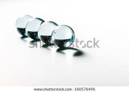 4 glass marbles in a row on white background - stock photo