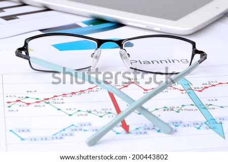 Glasses lying on a business graph analysis report. Digital tablet beside - stock photo