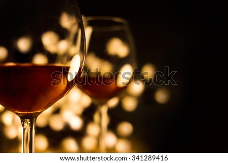 2 glasses of red wine with illumination lights background. Romantic dinner dating night.