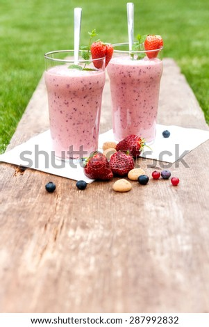 2 glasses with a berry milkshake and decoration - stock photo