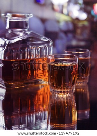 glasses with whiskey on a glass table - stock photo
