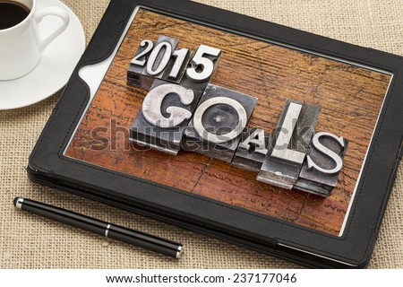 2015 goals - New Year resolution concept - text in vintage metal type blocks against grunge wood on a digital tablet with a cup of coffee - stock photo