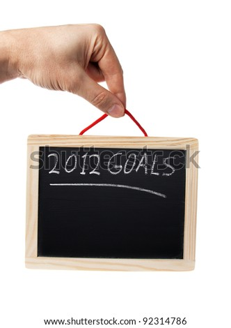 2012 goals on blackboard held by hand over white background