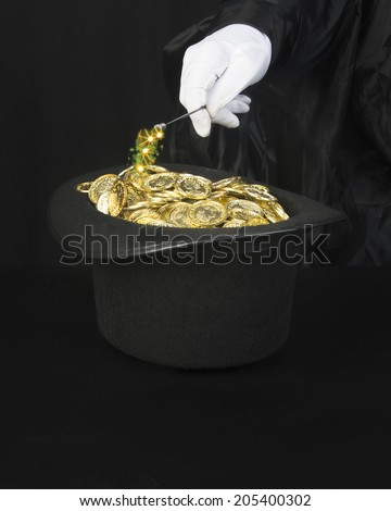 Gold in a hat/Magic Gold/Mysterious wand hat and a pile of gold in a magicians hat - stock photo