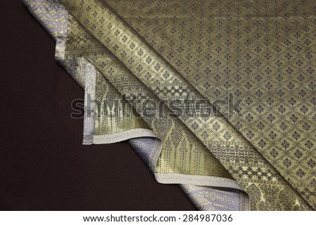 gold silk fabric fold background ,Line Thai background golden of light.Thailand pattern traditional gold background  with wave. golden pattern Thai silk style manual weaving, handcraft