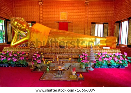 Gold statue of sleeping buddha covered in yellow cloth in local Thai temple, Bangkok - stock photo