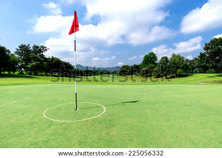 Golf course with flag and beautiful sky